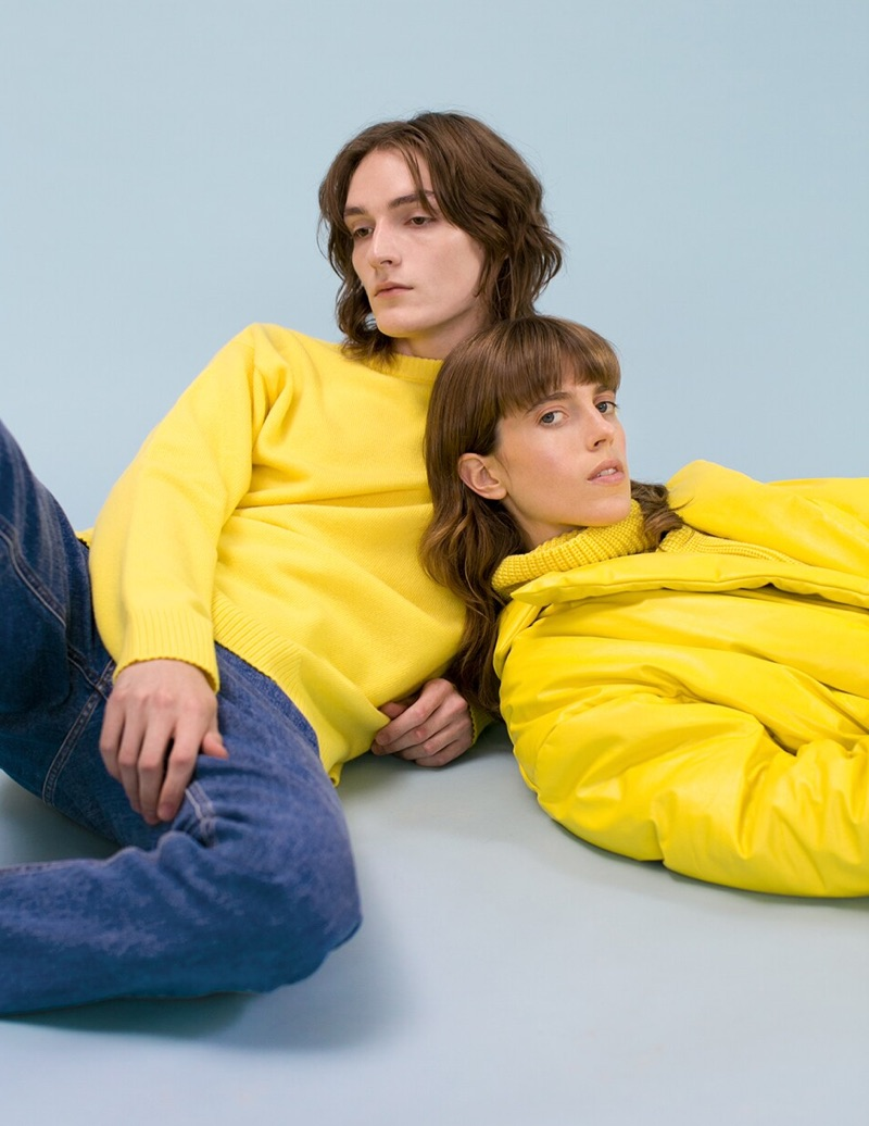 Posing with Sojourner Morrel, Alex Rychkov dons a yellow Loewe knit sweater $750 and Versace jeans $525.
