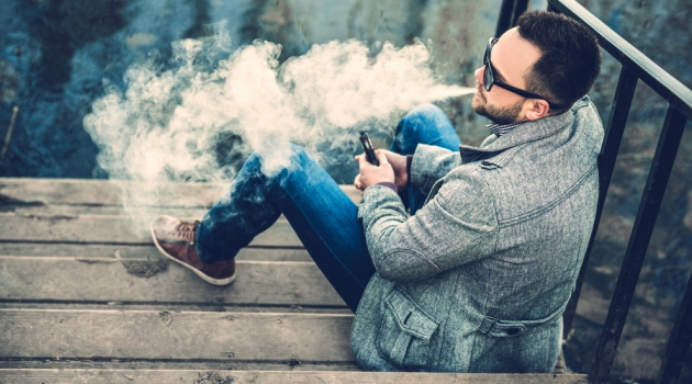 Man Vaping Outdoors in Sunglasses