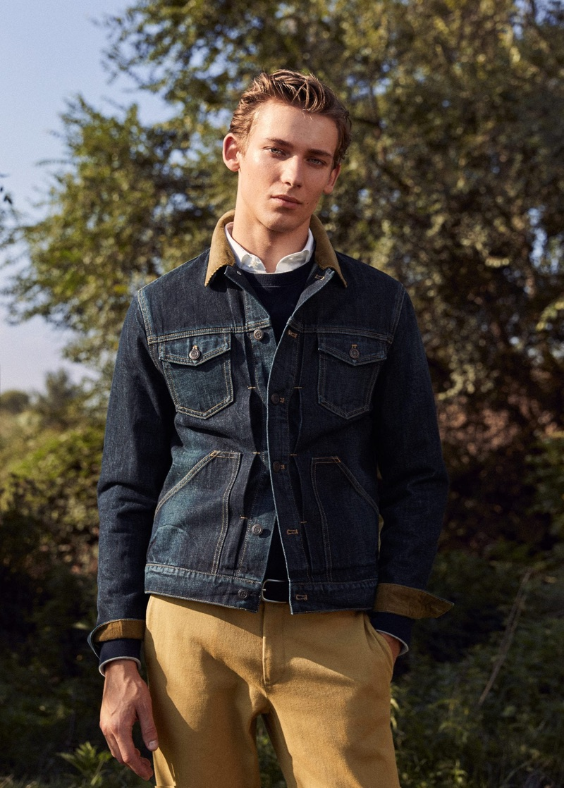 Sporting a classic men's outfit, Christoper Einla dons a jean jacket with khaki-colored pants by Mango.