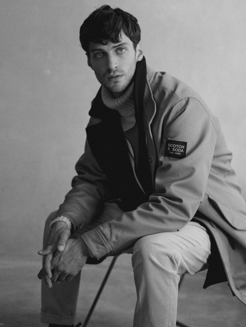 Sitting for a portrait, Matthew Bell wears Scotch & Soda's twill jacket $385 with a turtleneck sweater and pants.