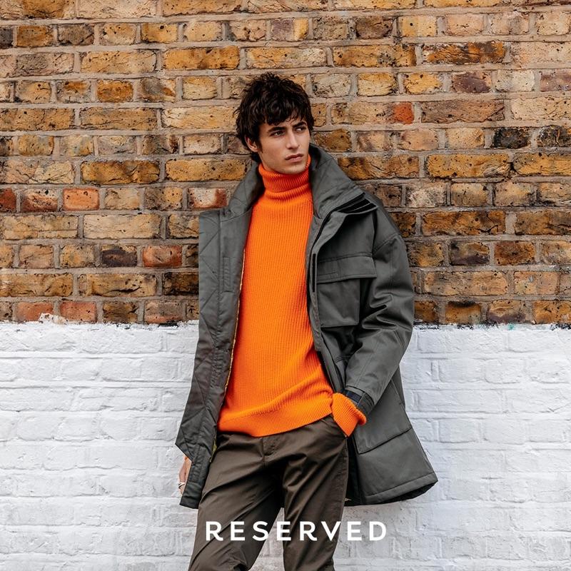 Making a stylish statement, Oscar Kindelan sports a parka with a ribbed orange turtleneck sweater.