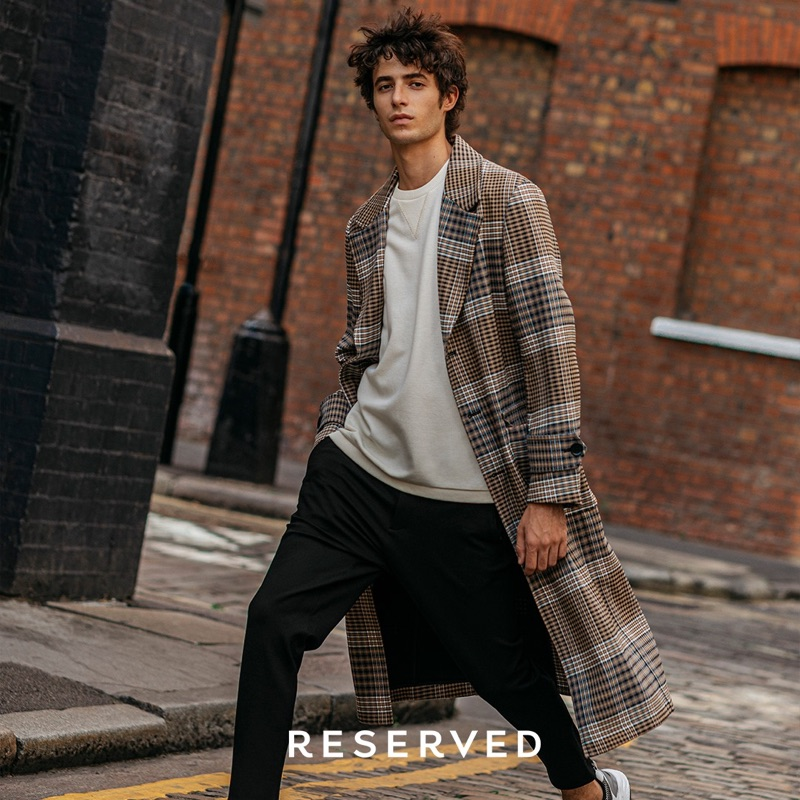 On the move, Oscar Kindelan wears a Reserved checked coat with a sweatshirt and trousers.