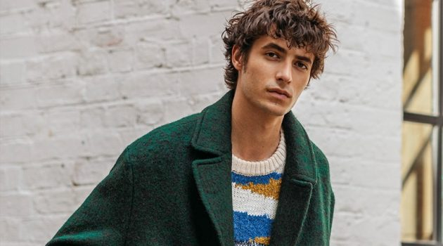 Oscar Kindelan dons a green coat with a graphic sweater from Reserved.