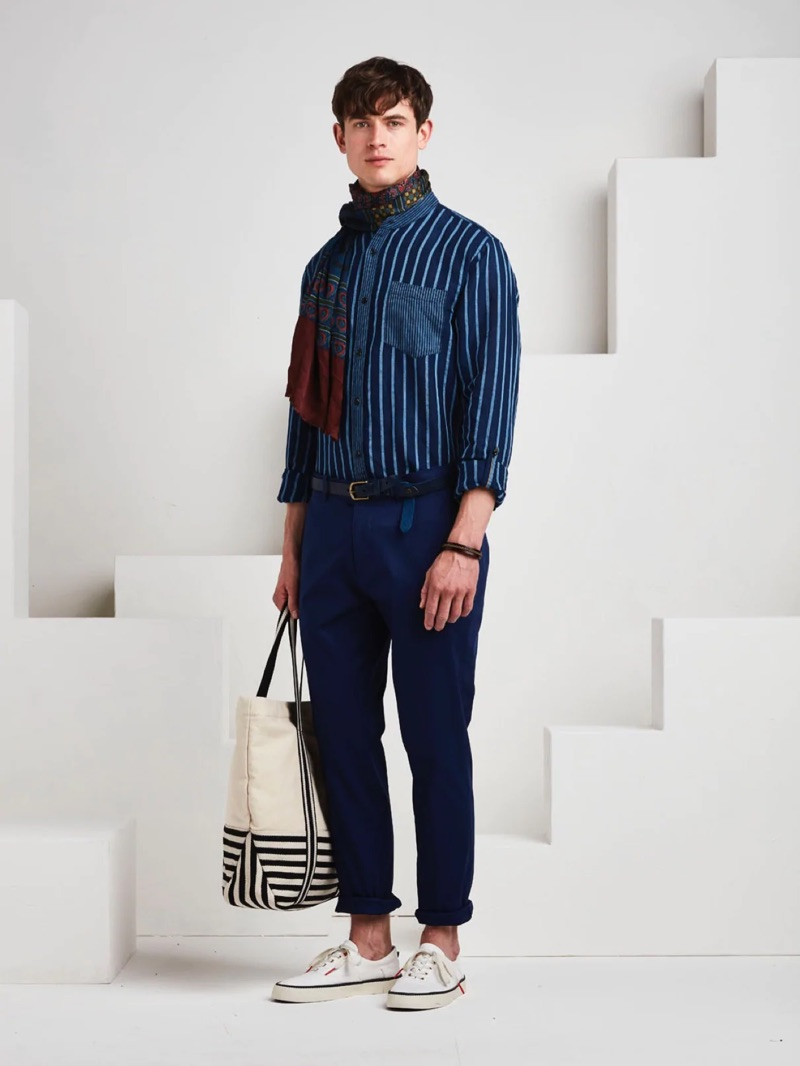Showcasing navy tones, Luc van Geffen wears a Scotch & Soda striped top with chinos, a patterned scarf, and a braided belt.