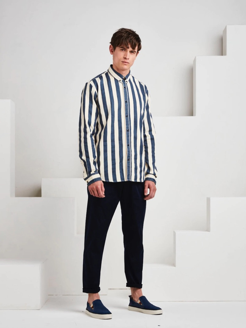 Luc van Geffen sports a striped shirt with chinos and slip-on sneakers for a smart look.