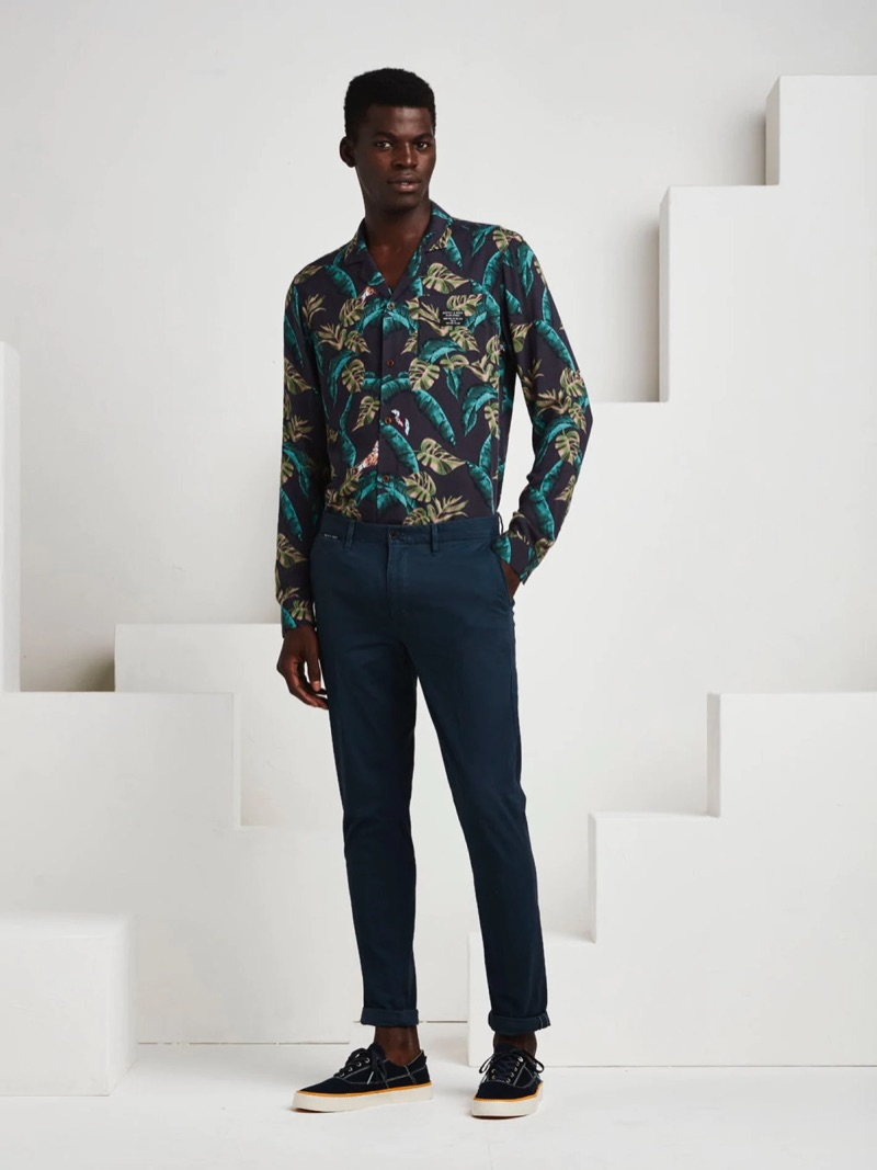 Donning a tropical print shirt from Scotch & Soda, Evandro Laurens also wears chinos and sneakers.