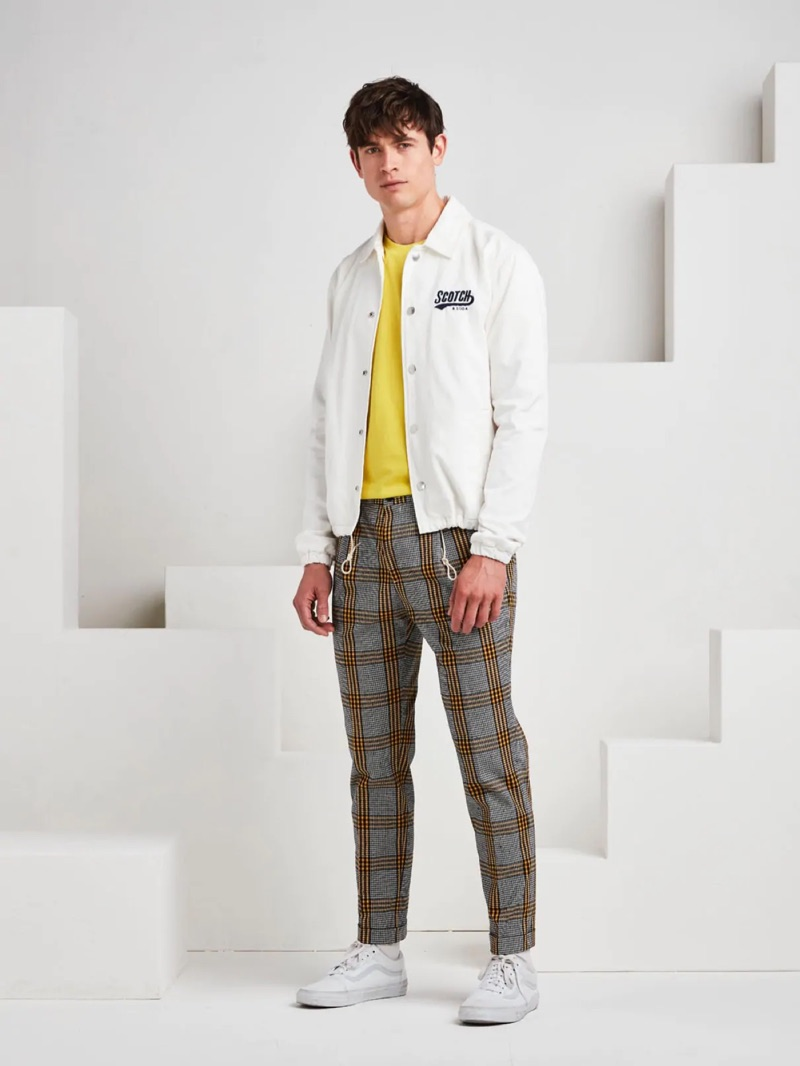 Going sporty, Luc van Geffen wears a Scotch & Soda coach jacket with plaid chinos and white sneakers.