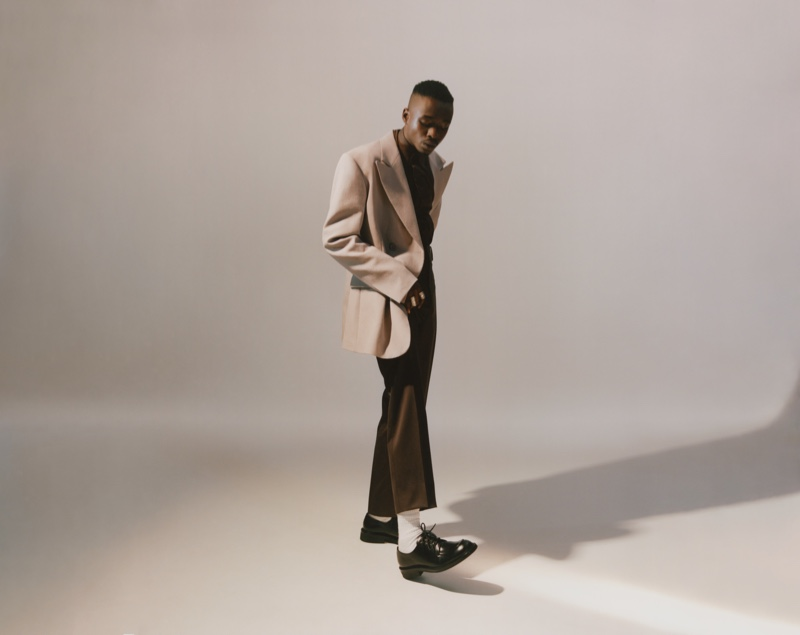 Taking to the studio, Ashton Sanders wears a Raf Simons blazer, Bianca Saunders shirt, Lemaire trousers, Gucci socks, and Prada shoes.