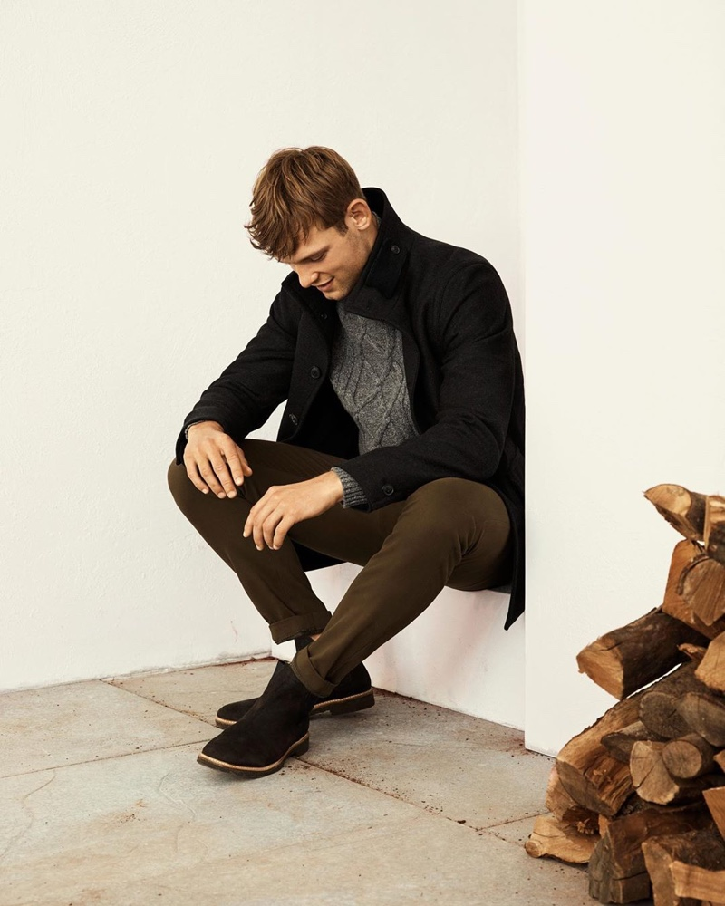 British model Elliott Reeder dons a gray cable-knit sweater with a black coat and chinos from Banana Republic.