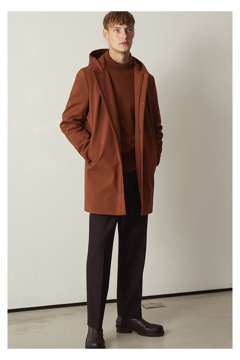 Embracing autumnal tones, Roberto Sipos models a hooded coat with a sweater and trousers by COS.