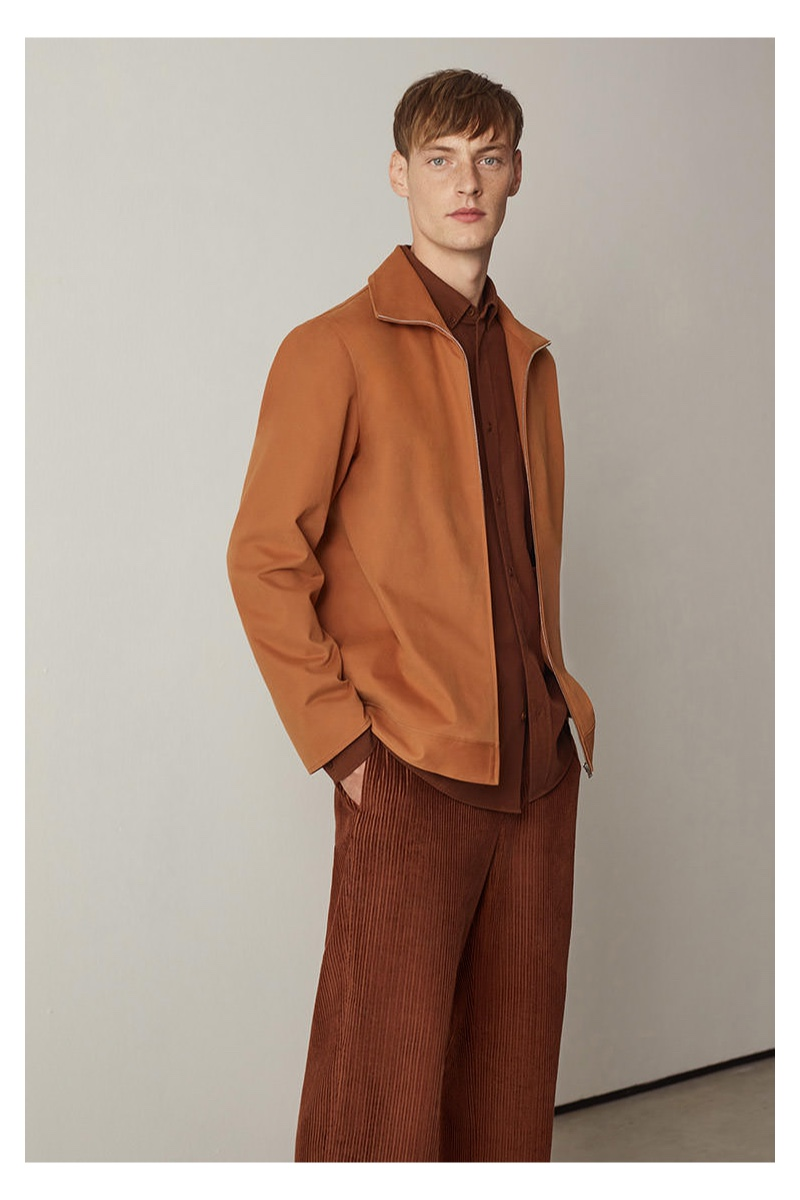 Connecting with COS, Roberto Sipos sports a full-zip shirt with wide-leg corduroy pants.