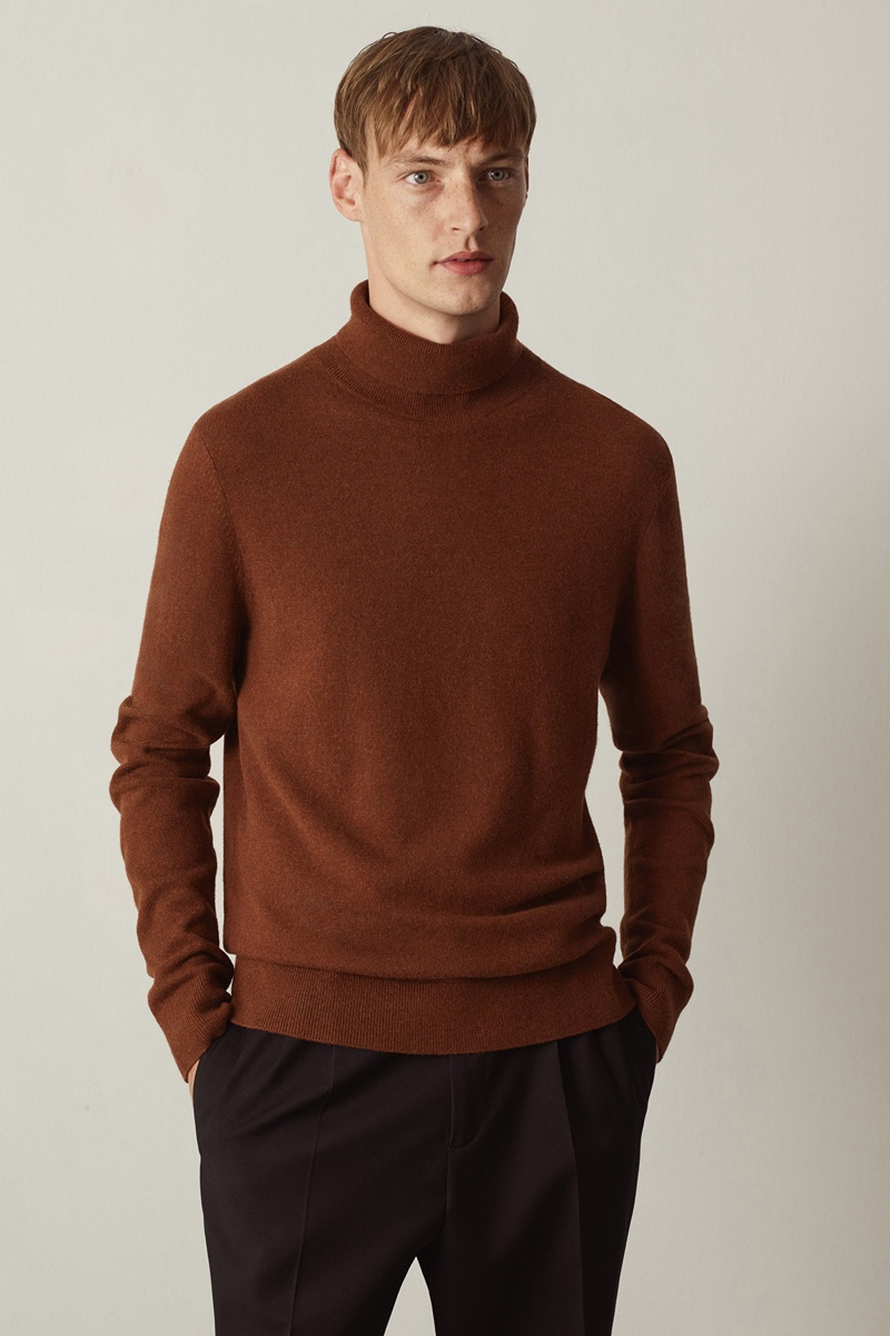 Front and center, Roberto Sipos sports a COS turtleneck sweater with pleated trousers.
