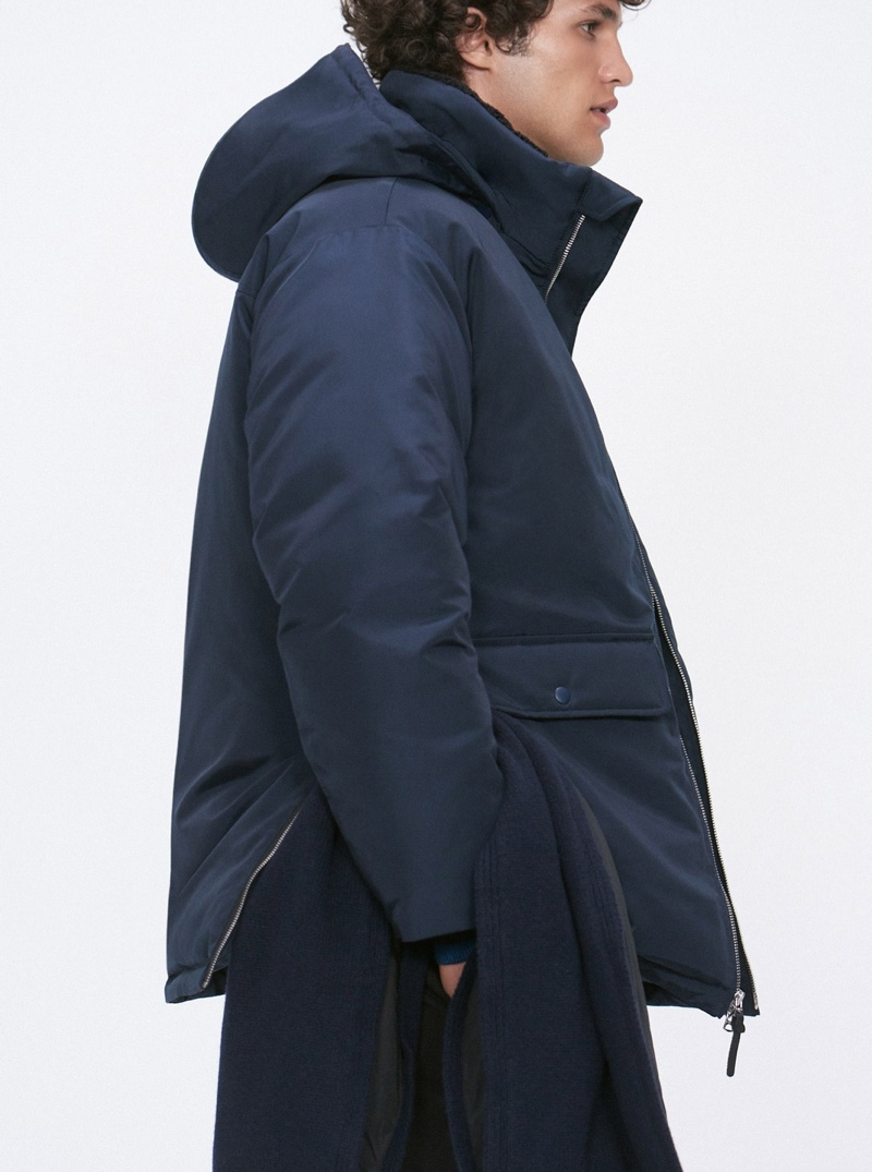 Delivering a side view, Francisco Henriques dons a Club Monaco down puffer jacket $450 in dark navy.