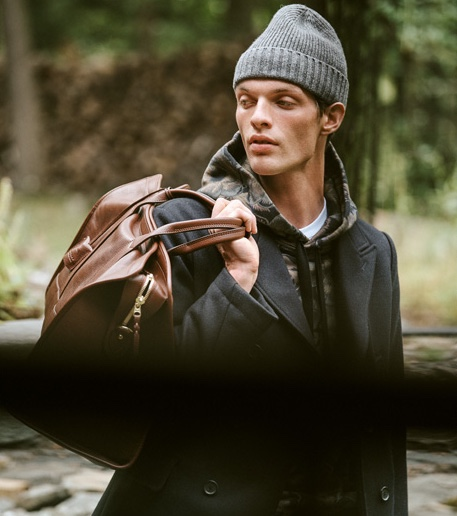 Rocky Harwood sports a Coach 1941 hoodie, Billy Reid peacoat, A.P.C. Petit Standard jeans, a Lotuff leather duffel travel bag, and Barbour beanie.