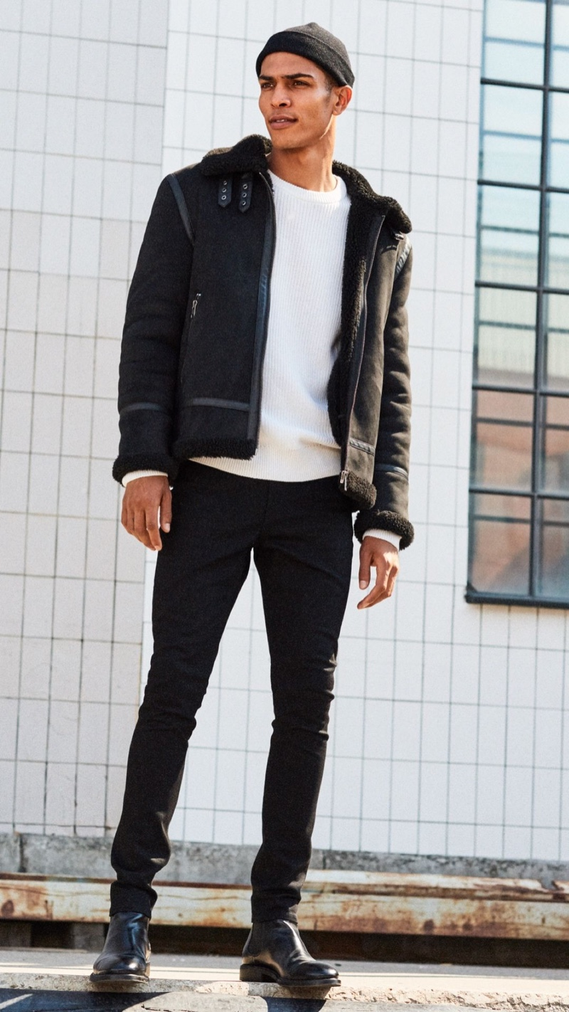 A trendy vision, Geron McKinley embraces black and white in a shearling jacket with skinny jeans and boots.