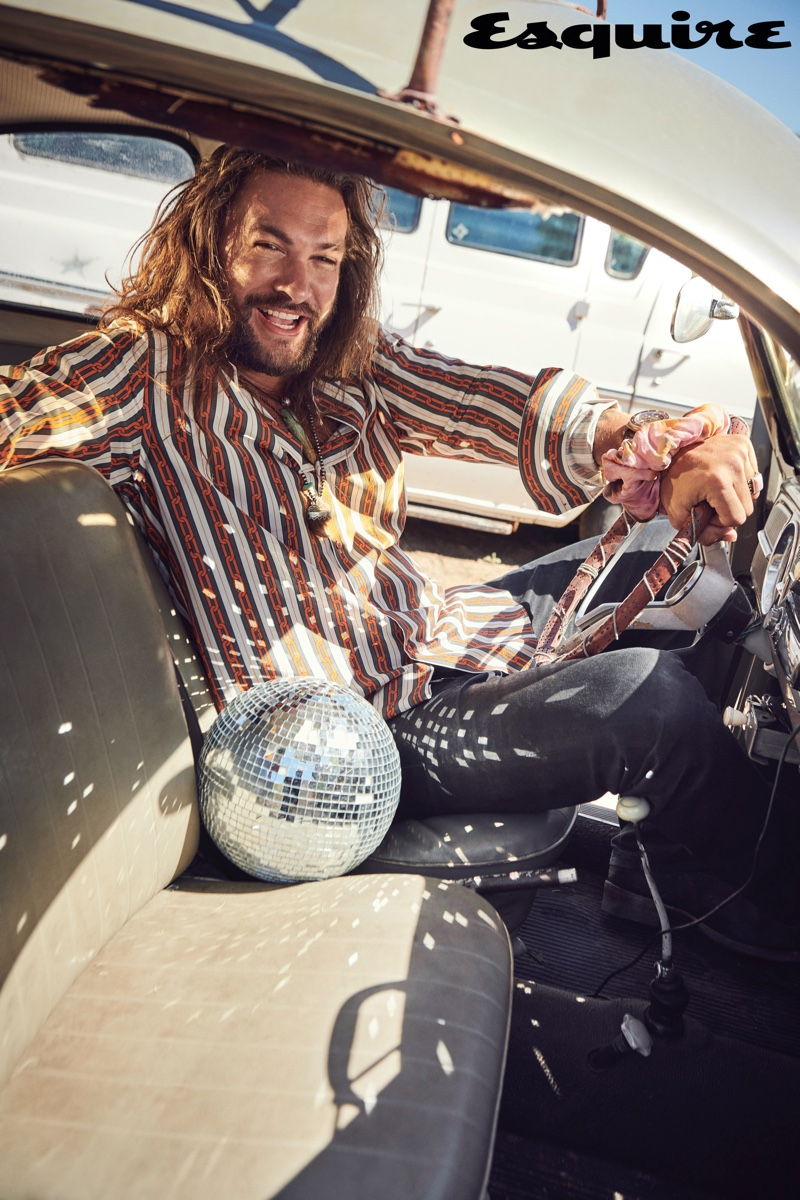 Actor Jason Momoa wears a Louis Vuitton shirt, Schaeffer jeans, Wesco boots, a Panerai watch, and Fendi scrunchie. He also dons necklaces from Rainbow Gems and Red Rabbit Trading Co.