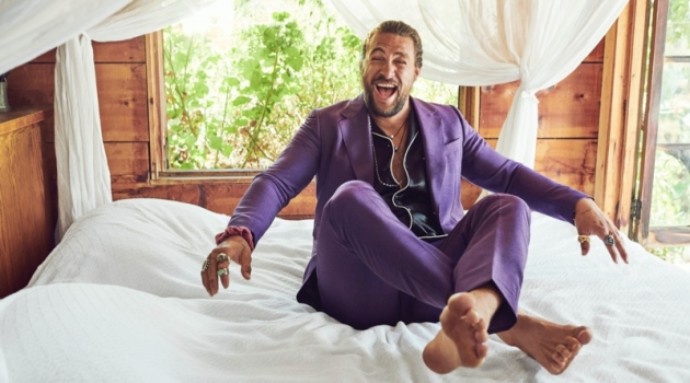 All smiles, Jason Momoa wears a shirt and purple suit by Gucci. His accessories put the spotlight on Rainbow Gems, Red Rabbit Trading Co., Book of Alchemy, and Leroy's Wooden Tattoos.