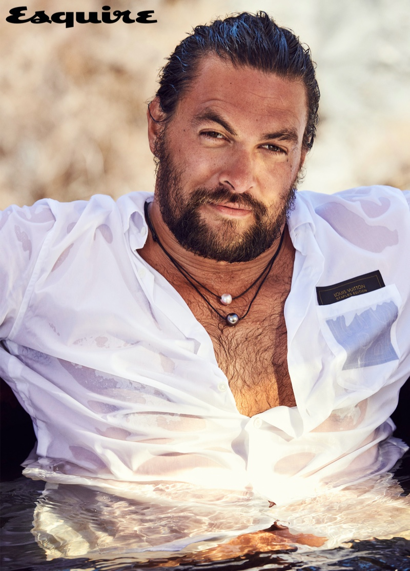 Connecting with Esquire, Jason Momoa wears a Louis Vuitton shirt with Rainbow Gems necklaces.