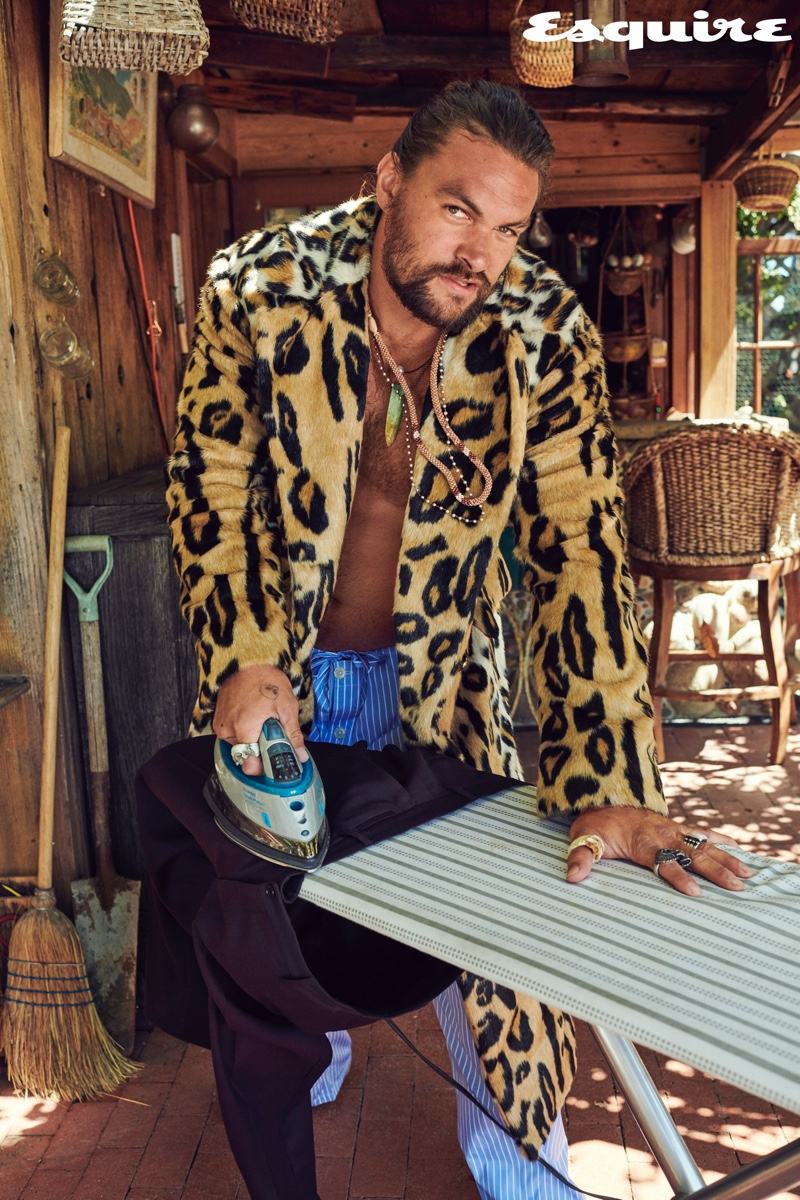 Making a statement in an animal print pattern, Jason Momoa wears a Versace coat. He also wears Paul Stuart pajama pants with necklaces by Rainbow Gems and Red Rabbit Trading Co. His rings come from Book of Alchemy and Leroy's Wooden Tattoos.