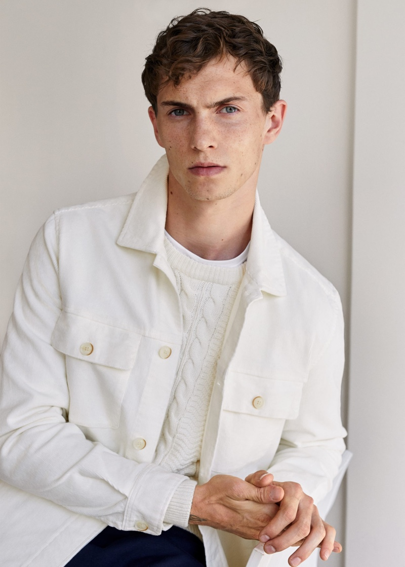 Luc Defont-Saviard wears a white shirt jacket and cable-knit sweater from Mango.