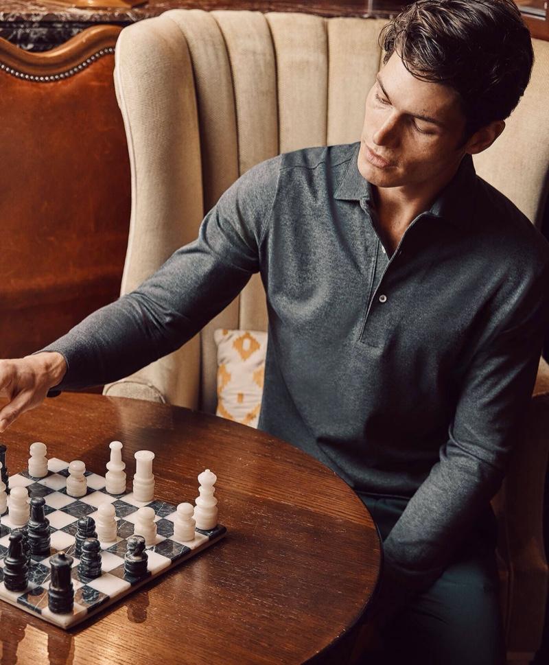 Playing a game of chess, Sam Way wears Luca Faloni's charcoal grey Brera polo shirt.