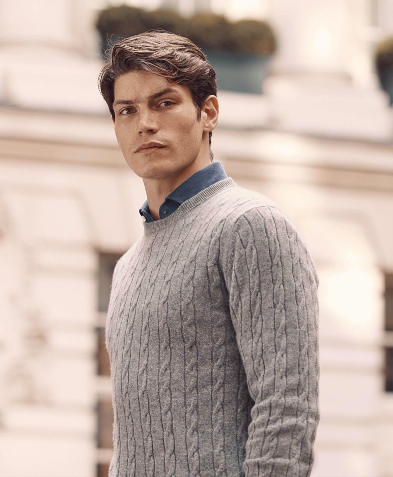 Connecting with Luca Faloni, Sam Way models a light grey cashmere cable knit sweater.