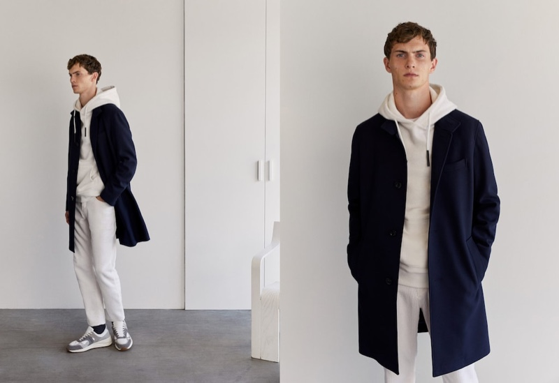 Making a case for neutrals, Luc Defont-Saviard dons an off-white hoodie and pants with a sleek navy coat by Mango.