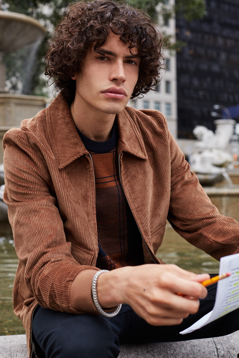 Front and center, Michael Cortina wears a brown corduroy jacket with a graphic top by Ben Sherman.