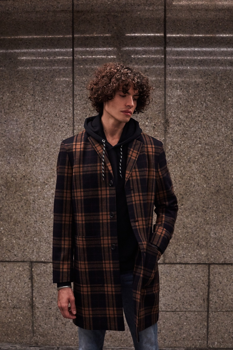 Donning a checked coat with a hoodie, Michael Cortina wears Ben Sherman.