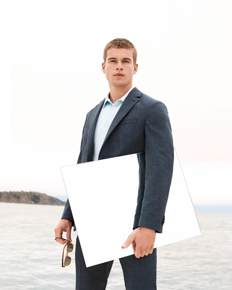 Model Mitchell Slaggert wears a navy suit with a light blue shirt by Banana Republic.