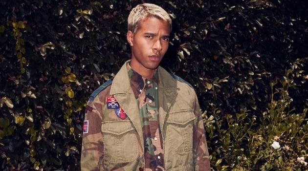 Embracing camouflage prints, Daouda Ka wears a POLO Ralph Lauren oxford shirt $98, hybrid jacket $498, and pants $188.