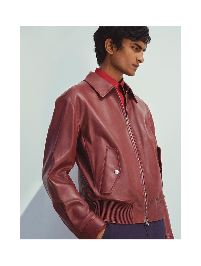 Making a color statement, Rishi Robin dons a red leather jacket by Alexander McQueen.