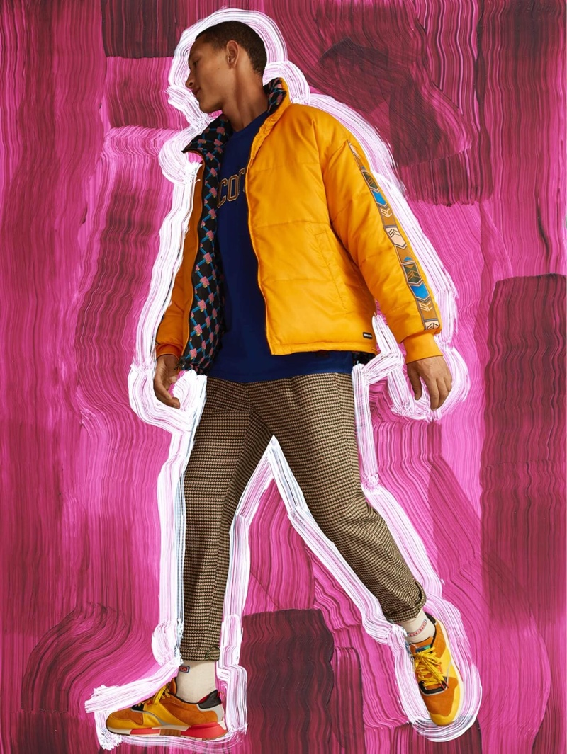 Embracing vibrant colors, Bruno Sitton rocks a Scotch & Soda reversible puffer jacket $275 in yellow.