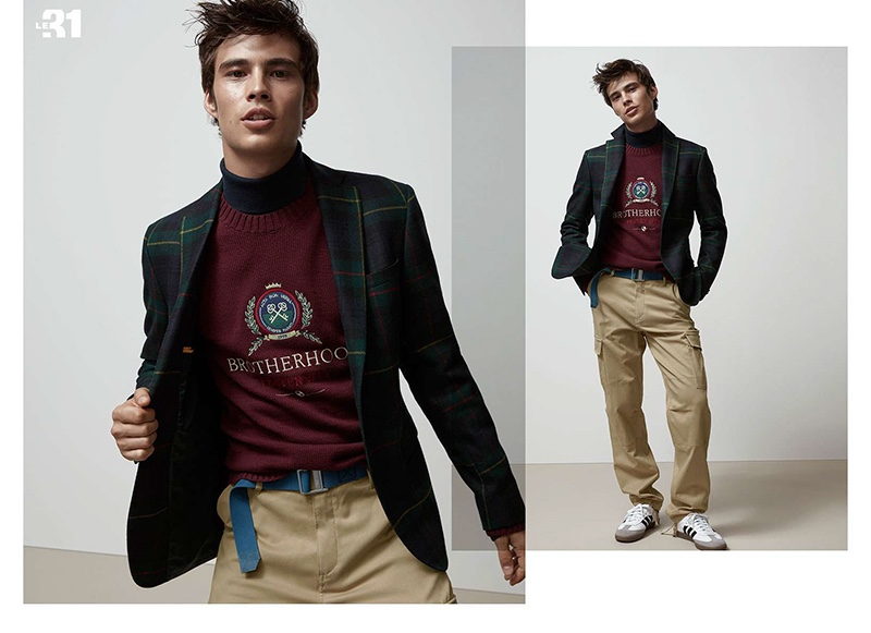 Embracing preppy style, Louis Baines wears a LE 31 plaid suit jacket, varsity club sweater, turtleneck, and cargo pants. He accessorizes with an Arcade belt and Adidas Original sneakers.