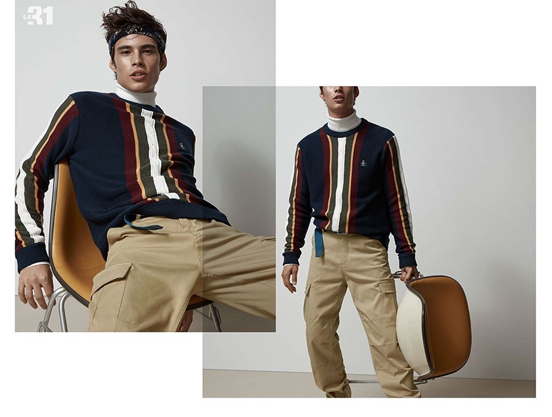 Front and center, Louis Baines sports a LE 31 block striped sweater, turtleneck, cargo pants, and bandana.