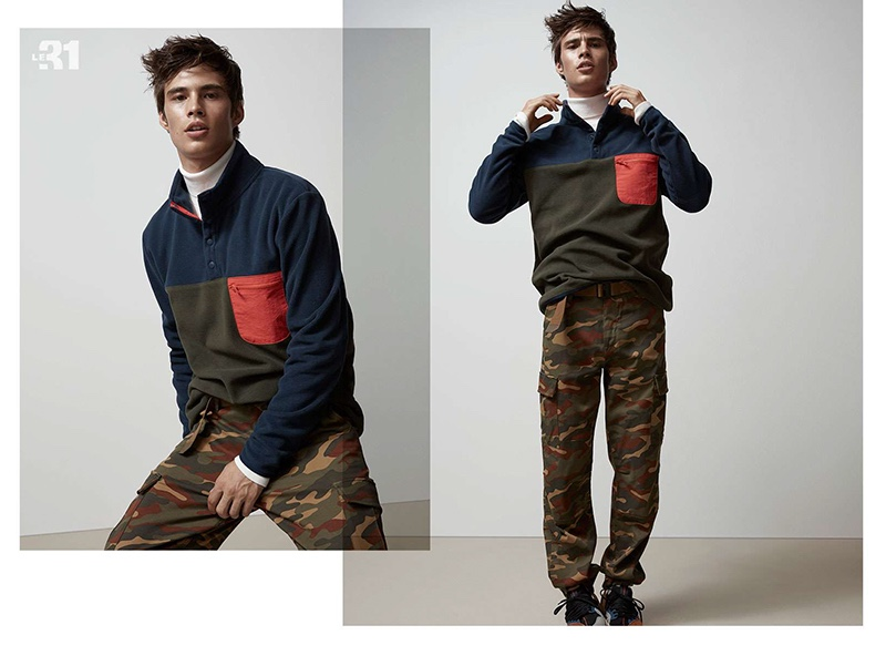 Model Louis Baines rocks a LE 31 fleece sweatshirt, turtleneck, and camouflage print cargo pants.
