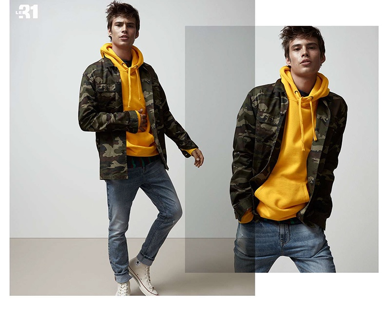 Going casual, Louis Baines wears a LE 31 camouflage print overshirt, yellow hoodie, and slim-fit jeans with Converse Chuck 70 canvas high top sneakers.