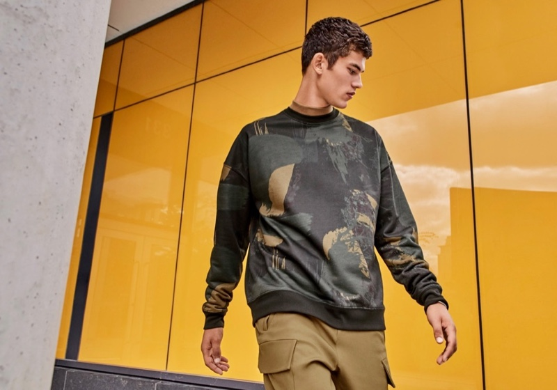 Going sporty, Finn Hayton dons a dark abstract sweatshirt by LE 31.