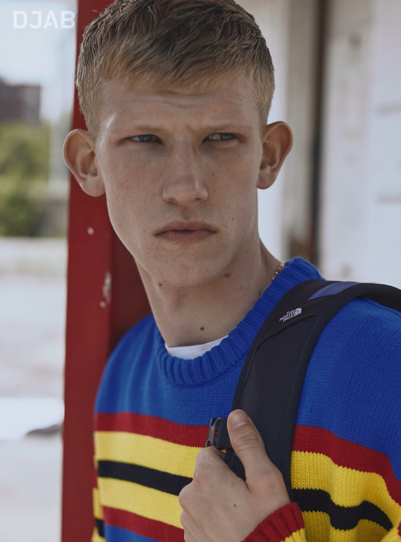 Connor Newall models a colorful DJAB sweater with a backpack by The North Face.