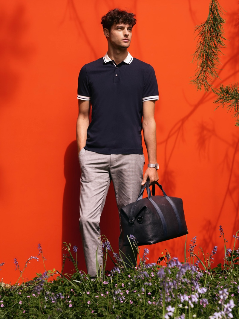 Front and center, Hannes Gobeyn dons a Ted Baker polo shirt with smart trousers.