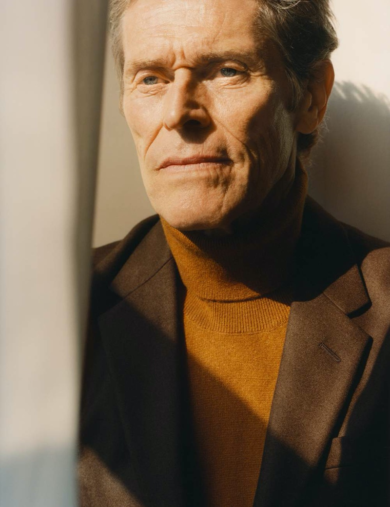 A smart vision, Willem Dafoe sports a Prada wool suit jacket and turtleneck sweater.