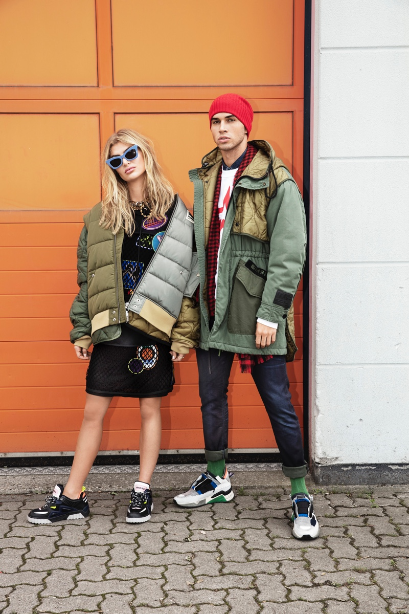 Appearing alongside Allie Fosheim, Daniel Angulo embraces a sporty look. The model dons a Diesel parka, sweatshirt, and jeans with a Wormland scarf. He also sports a HUGO knit beanie.