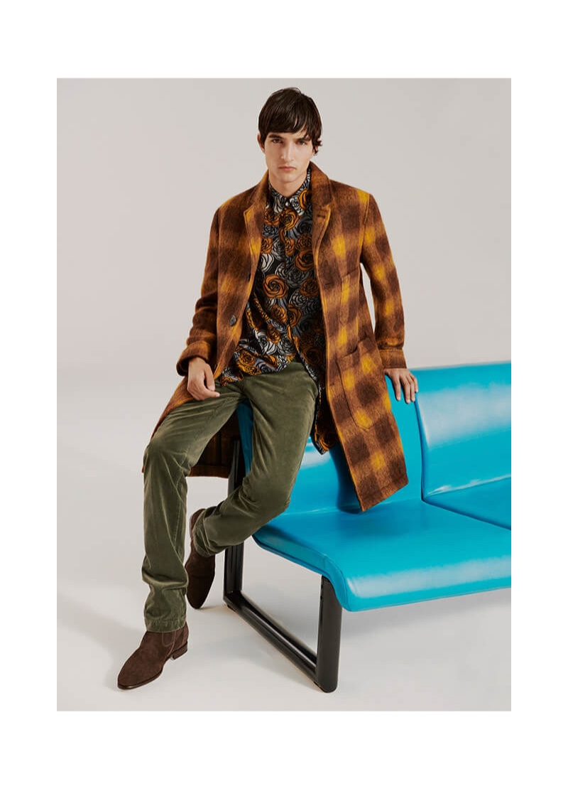 Connecting with YOOX, Pablo Fernandez dons a checked coat by AMI with a Versus Versace shirt and Acne Studios pants.