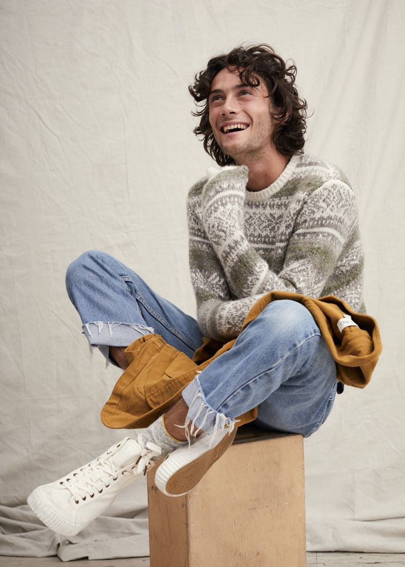 All smiles, Oli Green sports a fairisle sweater with light wash denim jeans from Alex Mill.