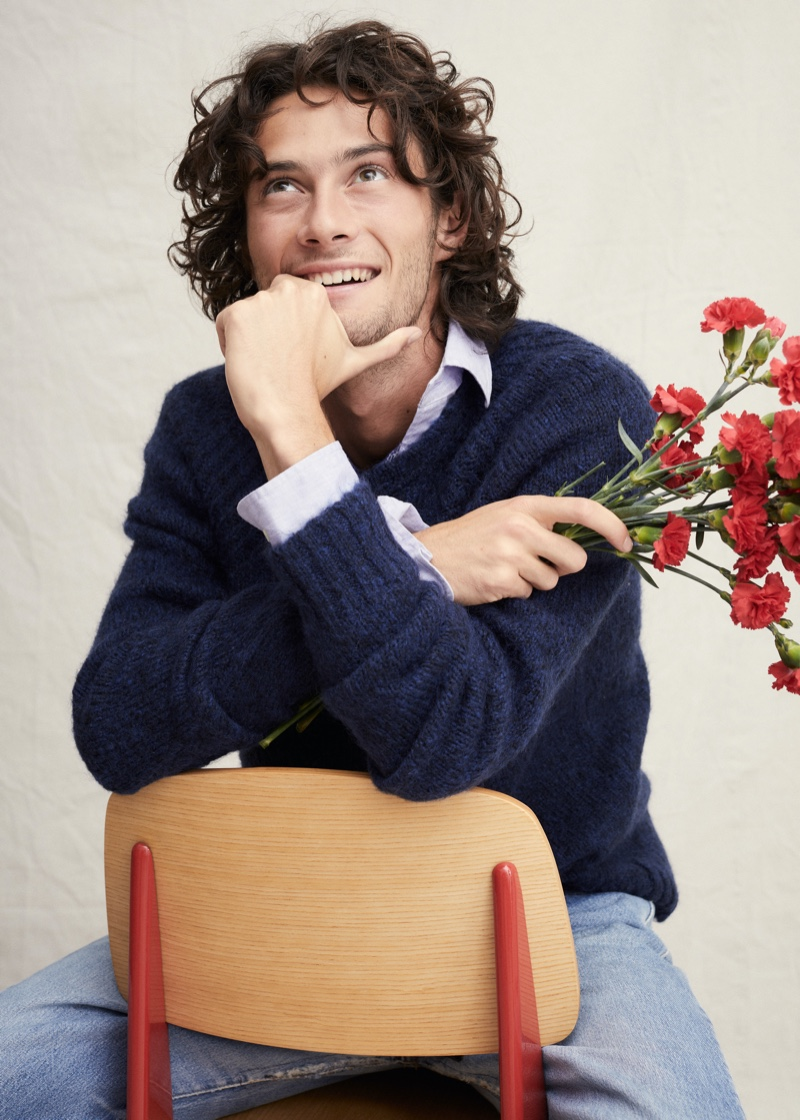 Pouring on the charm, Oli Green models a navy sweater with a button-down and jeans from Alex Mill.