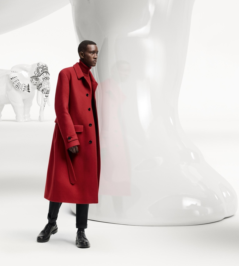 Making a statement in a red coat, Oumar Diouf fronts the BOSS x Meissen holiday campaign.