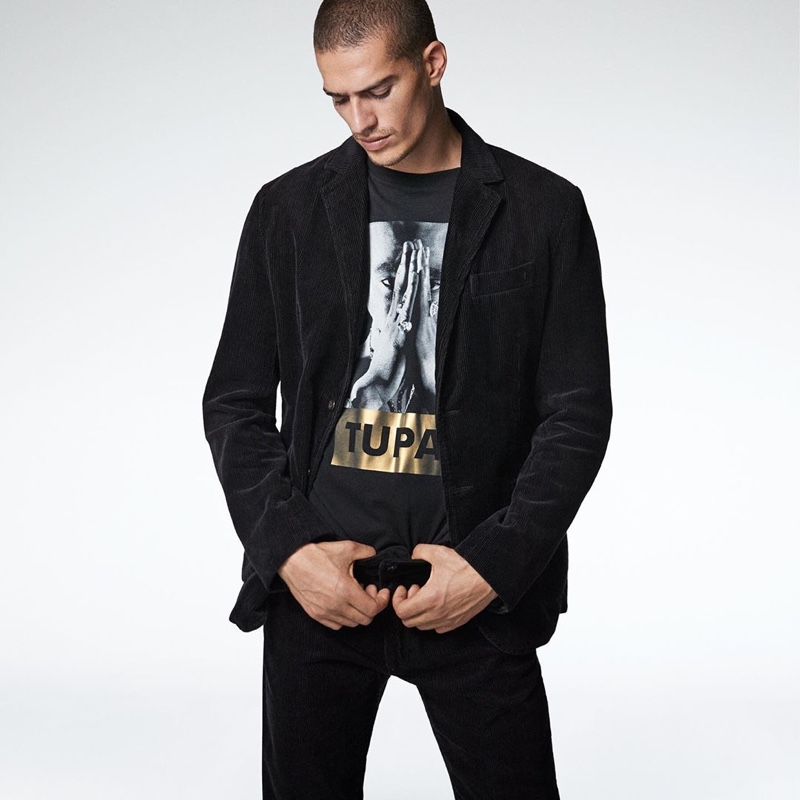 Marco Vinante dons black jeans with a graphic tee and a blazer from Replay.