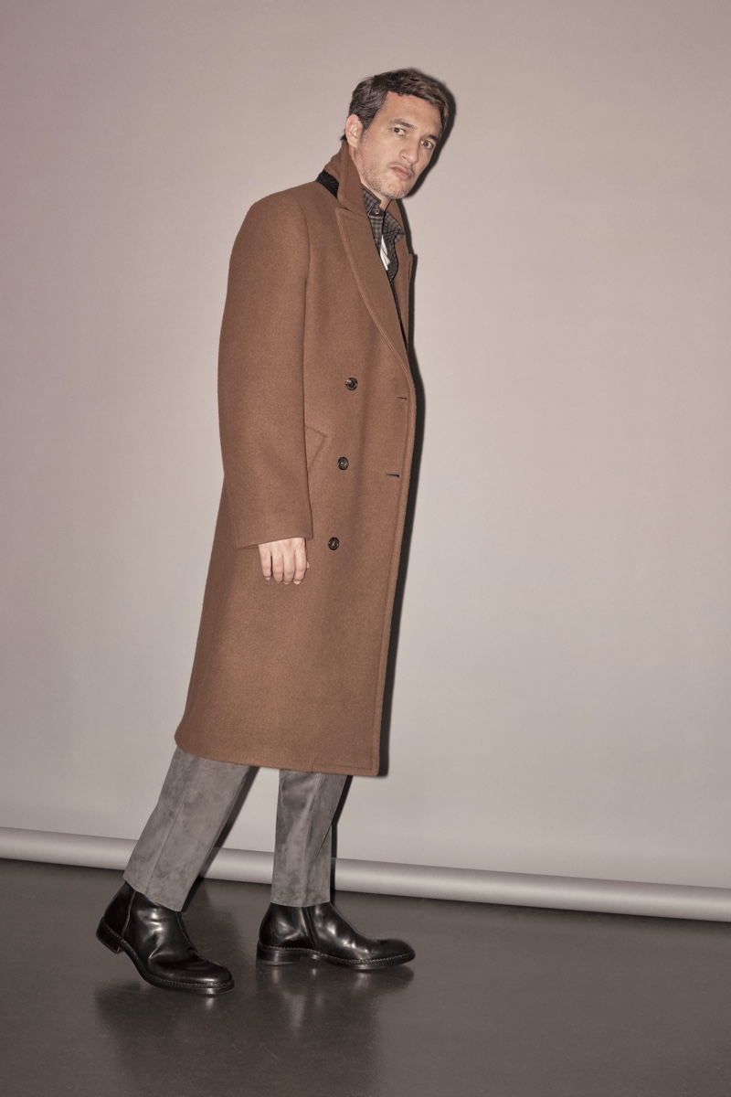 Ilay Kurelovic dons a long brown coat from Brioni's fall-winter 2019 collection.