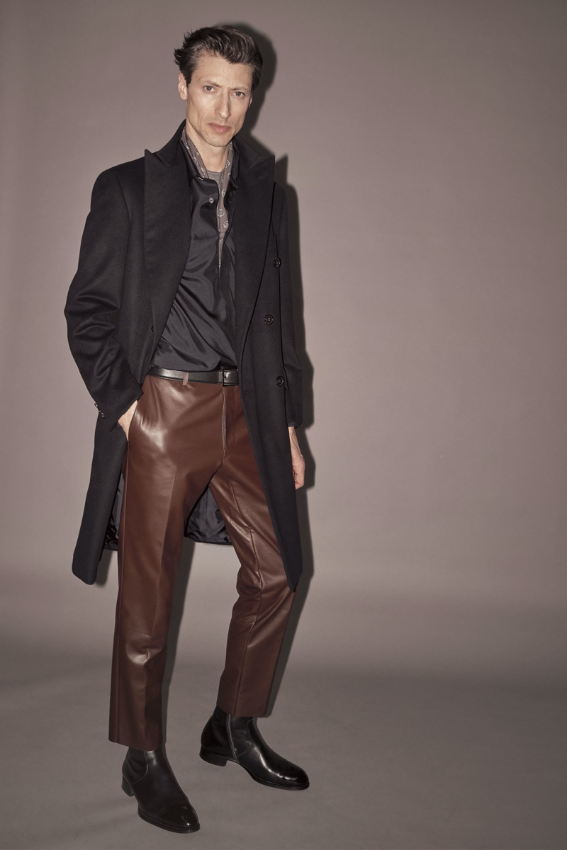 Jonas Mason rocks brown leather trousers with a long coat from Brioni's fall-winter 2019 collection.