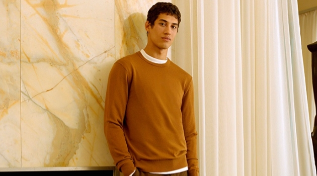 Malik Al Jerrari sports a brown sweater with wool flannel trousers from Club Monaco.